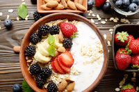 Flat lay top view at Fruit healthy muesli with banana strawberry almonds and blackberry with yogurt  in clay dish on wooden kitchen table