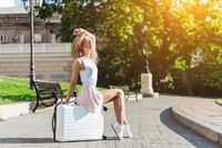 Girl traveler with a white suitcase