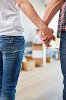 Glückliches Paar hält Hände beim Umzug