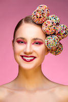 beautiful girl with candies on pink backgroound