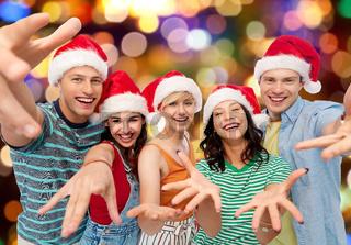 happy friends in santa hats over festive lights