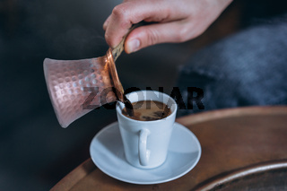 Man's hand pours coffee into a cup