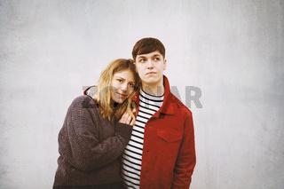 junges Paar vor Betonwand mit Textfreiraum