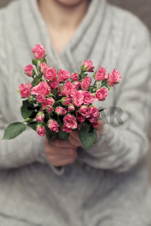 bouquet of bush of roses in female hands on a background