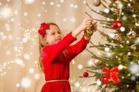 happy girl in red dress decorating christmas tree