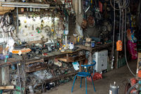 A messy chaotic electrical repair workshop with spare parts and empty chair.