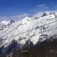 Ski resort with chair lift and snow mountains at nice sunny day