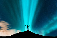 Aurora and silhouette of standing man with raised up arms
