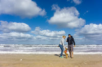 Man and woman standing at he beach with their little cute dog