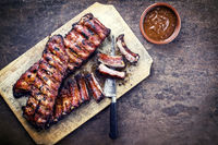 Barbecue spare ribs St Louis cut with hot honey chili marinade as top view on a rustic cutting board with copy space