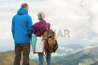 A pair of hipster tourists is standing next to each other in the mountains against the backdrop of the plateau of valleys and sky. Rest in the mountains. Traveling in pairs
