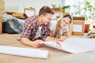 Glückliches Paar bei der Planung von Hausbau