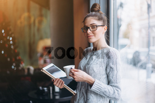 Young girl looking at tablet and smiling in cafe with big window.