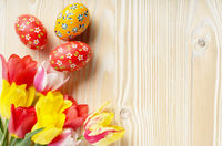Colorful tulip flowers and easter eggs on wooden table background with space for text