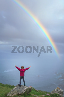 Girl on the top of a rock looking at rainbow