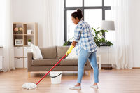 african woman or housewife cleaning floor at home
