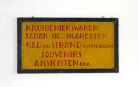 Sign saying 'groceries, tabaco, cigarettes, bath, beach, souvenirs and postcards' in dutch