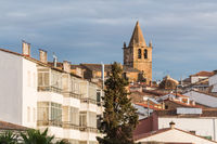 Views of San Blas with the Church of Santiago in the background illuminated by the light of the sunset in Caceres.