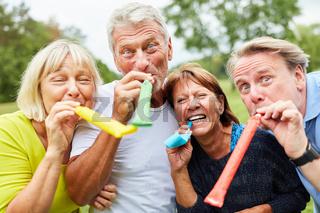Gruppe Senioren feiert mit Tröten Geburtstag