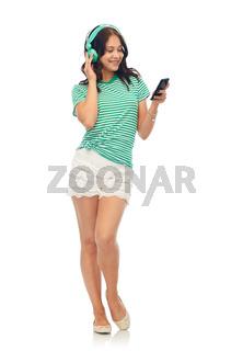 happy teenage girl in headphones with smartphone