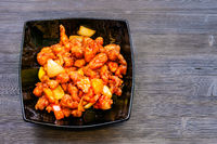 Sweet and Sour Chicken in black bowl on dark table