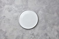 Decorative ceramic empty white handmade plate presented on a gray concrete background with copy space for your menu. Flat lay