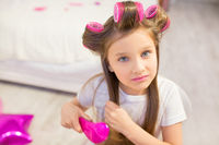 Cute girl brushing her hair.