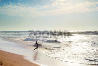 Surfer running to surf