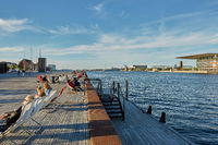 People relaxing and enjoying afternoon's sun with The National Opera House