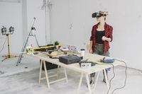 Woman using virtual reality goggles in workshop