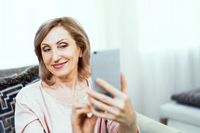 Beautiful mature woman takes selfie at home