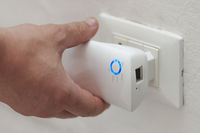 White man insert a wifi repeater in a wall plug