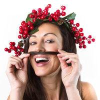 Smiling woman with a christmas wreath on her head, playing with her hair