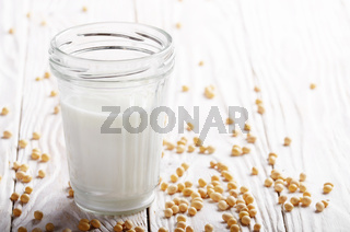 Non-dairy alternative Soy milk or yogurt in mason jar on white wooden table with soybeans aside