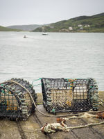 Crab traps on the pier bay and boats in the background