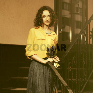 Happy young fashion woman in yellow shirt with bouquet of flowers