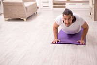 Young man doing physical exercises at home