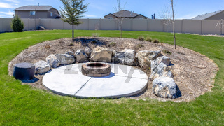 Panorama frame Circular fire pit surrounded by rocks in the middle of the grassy yard of a home
