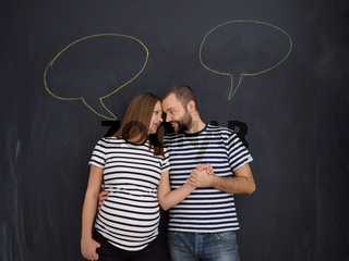 pregnant couple posing against black chalk drawing board