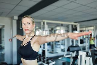 Frau beim Arme strecken im Fitnesscenter