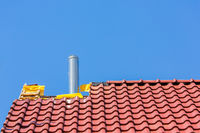 New roof with roof tiles and chimney pipe