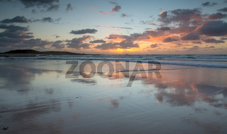 Mirrored coastal reflections in wet beach sand at sunrise