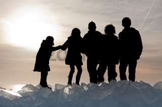 Silhouette of children on Ice hummocks at sunset in the Netherlands