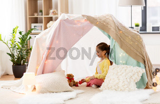 little girl playing tea party in kids tent at home