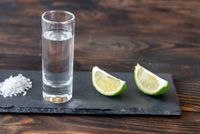 Glass of tequila with lime wedges