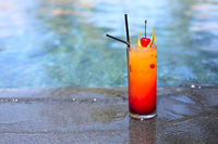 Glass with a bright tequila sunrise cocktail by the pool.