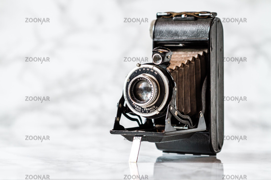 Vintage Folding Camera on Marble Background