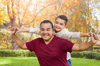 Mixed Race Hispanic and Caucasian Son and Father Having Fun At The Park