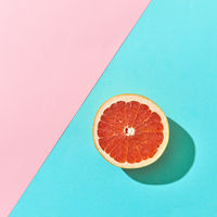 Juicy half of citrus grapefruit on a blue-pink cardboard background with copy space. Top view