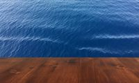 old brown oak wooden deck table on the blue sea background, wood table